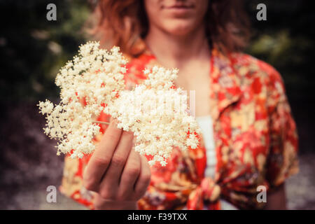 A young woman is holding a bunch of elderflowers she has been picking - Stock Photo