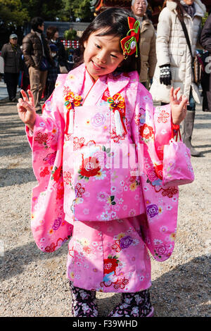 Japanese child, girl,4-5 years old, outdoors in winter sunlight, posing for viewer while wearing pink kimono. Smiling, - Stock Photo