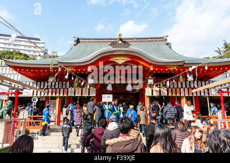 The Ikuta Shinto shrine in Kobe at New year. In front of the main hall with crowds of people and blue vested security - Stock Photo