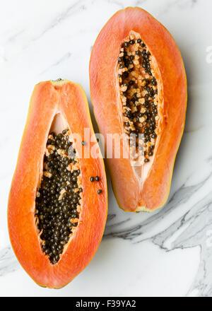 A Papaya cut in half on marble surface