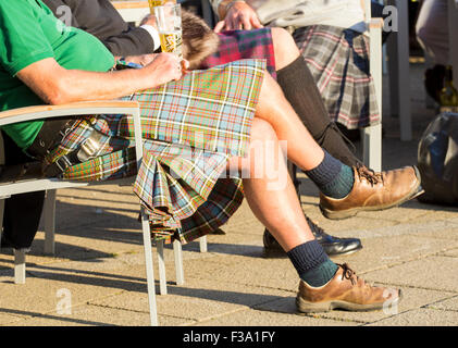 Scottish men wearing kilts enjoying a beer outside pub. - Stock Photo