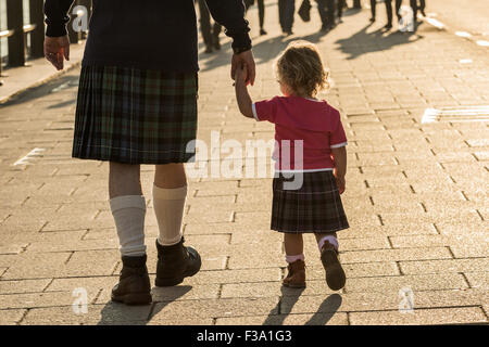 Rear view of man and child wearing kilts; national dress of Scotland. - Stock Photo