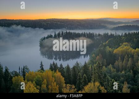 Foggy HDR aerial view of the Aulanko nature reserve park in Finland. The sun hits the fog above the lake in the - Stock Photo
