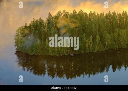 Foggy peninsula in the Aulanko nature reserve park in Finland. The sun hits the fog above the forest in the early - Stock Photo