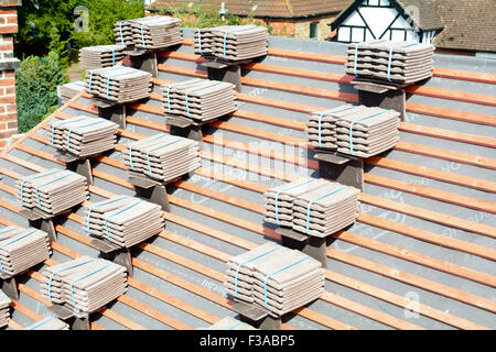 Roof tiles stacked in piles on wooden battens ready for fixing to roof in Bedford, Bedfordshire, England - Stock Photo