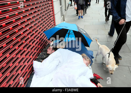 Two young homeless people sleeping rough on the pavement at Bishopsgate London England UK  KATHY DEWITT - Stock Photo