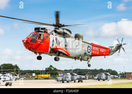 Royal Navy Westland Sea King HU5 search and rescue helicopter hovering - Stock Photo