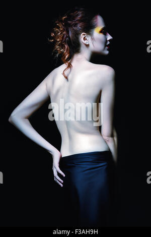 Gloomy portrait of a vampire woman among the dark. Rear view - Stock Photo