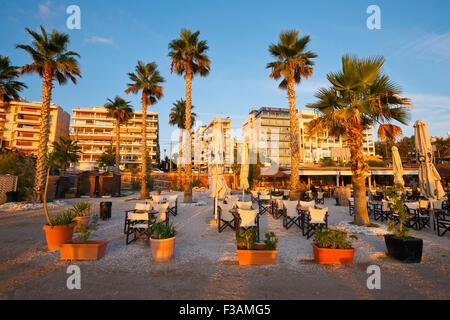 Umbrellas and tables on the beach in Palaio Faliro in Athens, Greece - Stock Photo