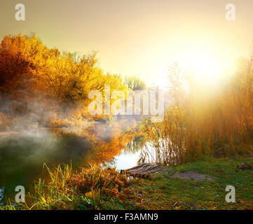 Fog over river in forest in the autumn - Stock Photo