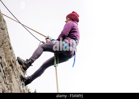 Female rock climber abseiling with safety rope and climbing harness on a rockface. North Wales, UK, Britain - Stock Photo