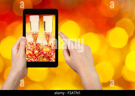 man takes photo of Christmas still life - two glasses of champagne with blurred background from big red and yellow - Stock Photo