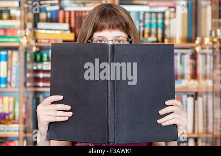 girl with glasses reads big book with blank cover in library - Stock Photo
