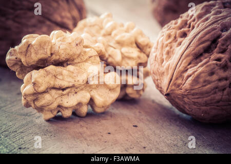 Walnuts on a wooden table in retro style. - Stock Photo