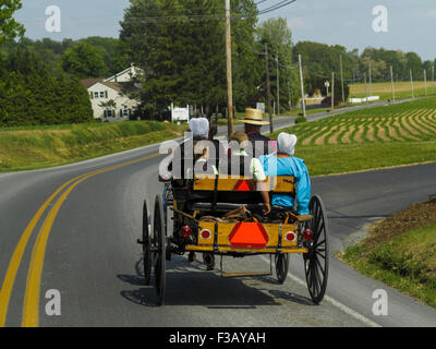 Amish family driving horse and buggy along country road Lancaster County Pennsylvania USA - Stock Photo