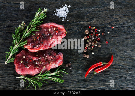 Two beef steaks garnished with a couple of rosemary twigs, dwarf chili peppers, sea salt granules and peppercorns - Stock Photo