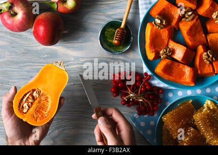 Autumn menu. Man hands holding little pumpkin and a knife against the background of fresh apples, a bunch of viburnum berries, h