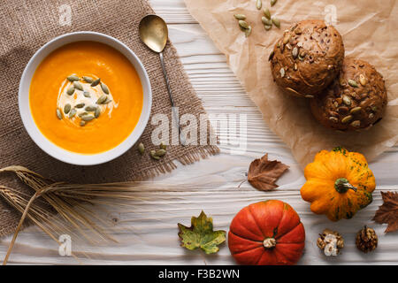 Traditional pumpkin soup with seeds and fresh just baked rye bans on a white wooden background.