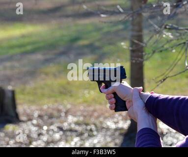 Target shooting with hand gun - Stock Photo