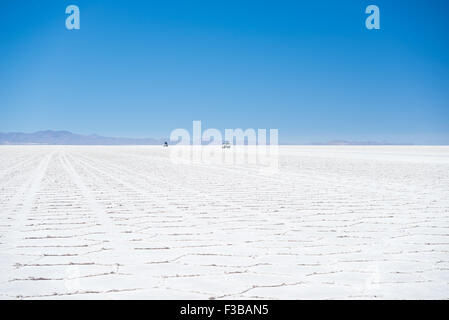 Two 4x4 vehicles in the distance exploring the world famous Uyuni Salt Flat, among the most important travel destination - Stock Photo