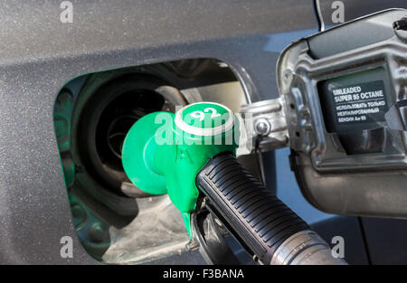 Closeup pumping gasoline fuel in passenger car at gas station - Stock Photo