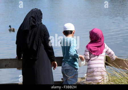 AUCKLAND - SEP 29 2015:Immigrants Muslim family feed ducks in a pond.New Zealand will take 750 Syrian refugees over - Stock Photo