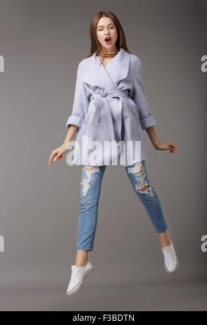 Trendy Young Female Jumping in Blue Coat - Stock Photo