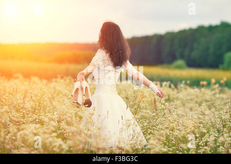 Young bride holding shoes walking on the flower meadow - Stock Photo