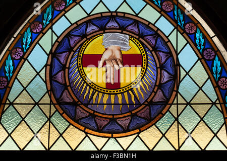 God the Father depicted as the Blessing Hand in the stained glass window by the Beuron Art School from the 1910s - Stock Photo