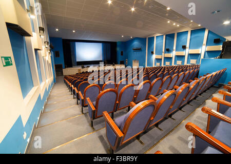 View from stairs on screen and rows of comfortable blue chairs in cinema room - Stock Photo