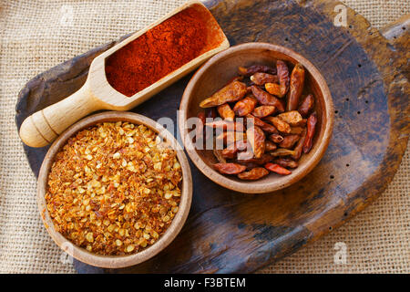 Chili pepper, dried in wooden bowl, crushed in a wooden bowl and as powder on wooden scoop is all on an old antique - Stock Photo