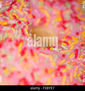 Close-up of a pink ring donut with coloured hundreds and thousands - Stock Photo