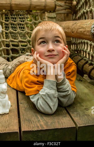 Six year old boy dreamily taking a break in a treehouse platform at Woodland Park Zoo, Seattle, Washington, USA - Stock Photo
