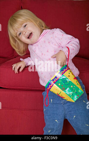 Toddler girl playing with a decorative paper bag, using it as her purse, as she leans on the sofa in Issaquah, Washington, - Stock Photo
