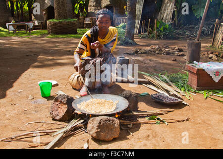 Dorse woman roasts coffee beans. Photographed in the Omo Valley, Ethiopia - Stock Photo