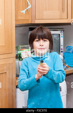 Mixed ethnicity, (Japanese English) 11 year-old boy firing party popper - Stock Photo