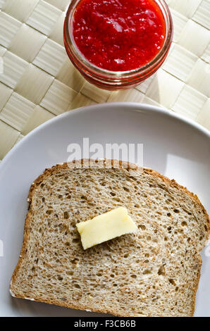 Slice of whole grain bread with pat of butter on a plate and small jar of homemade strawberry jam.  View from above. - Stock Photo