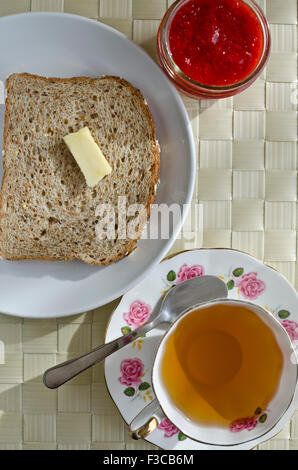 Slice of sprouted whole grain bread toast with butter, cup of tea in a fancy teacup and a jar of homemade strawberry - Stock Photo