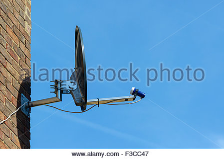 Satellite dish on house wall, Southampton, Hampshire, England, UK - Stock Photo