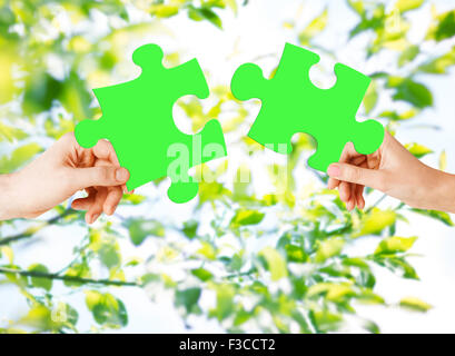 hands with green puzzle over natural background