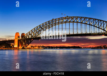 Side view of Sydney Harbour bridge at sunrise with scarlett sun light and illumination of still arch - Stock Photo