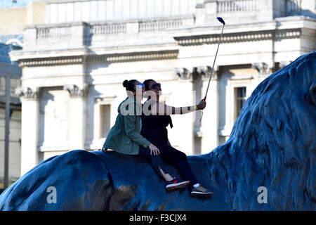 London, England, UK. Two young women sitting on a lion in Trafalgar Square taking a selfie - Stock Photo