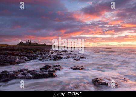 Dunstanburgh Castle sunrise, waves breaking over the rocky shoreline just along from Craster, Northumberland, UK - Stock Photo