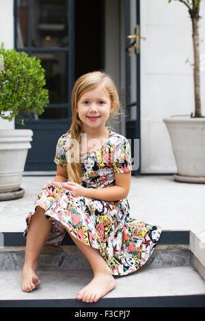 Little girl sitting on steps, portrait - Stock Photo