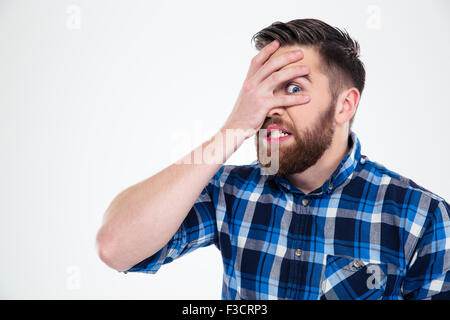 Portrait of a scared man covering his face with palm and looking at camera through fingers isolated on a white background - Stock Photo