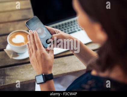 Close up shot of woman photographing a coffee of cup with her mobile phone while sitting at a cafe. - Stock Photo