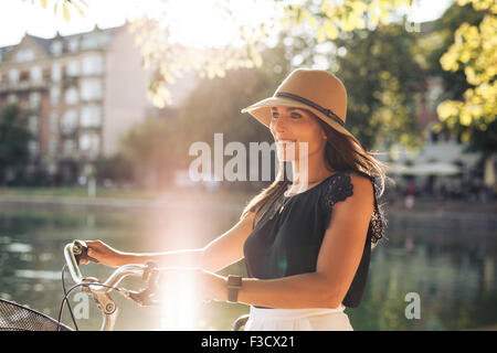Portrait of happy young woman at the city park walking along a pond with her bicycle. European female model wearing - Stock Photo
