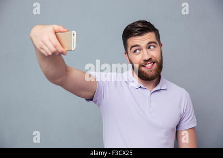 Portrait of a happy man making selfie photo on smartphone over gray background - Stock Photo