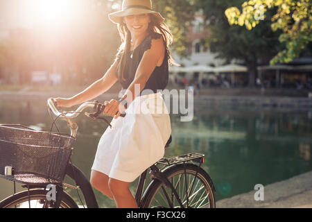 Portrait of happy young female cycling by a pond. Woman wearing a hat on a summer day riding her bicycle at city - Stock Photo