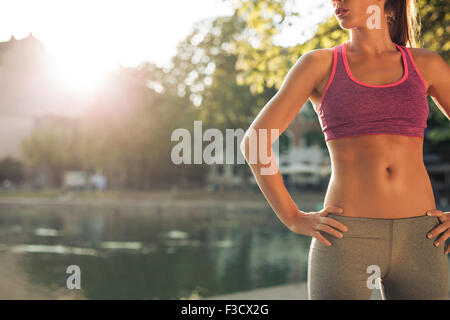 Cropped shot of fit young woman in sportswear standing with her hands on hips outdoors. Female runner ready for - Stock Photo